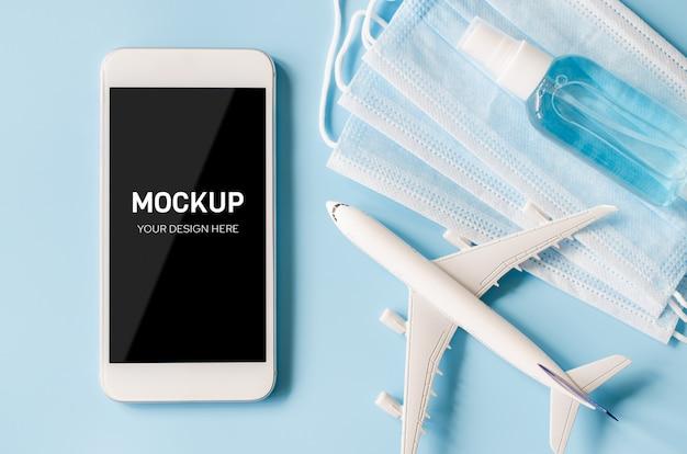 Макет смартфона с моделью самолета, маска для лица и дезинфицирующее средство.