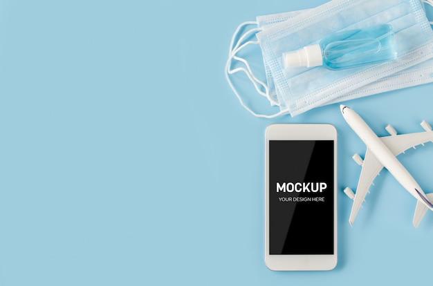 飛行機モデル、フェイスマスク、消毒剤を備えたスマートフォンのモックアップ。