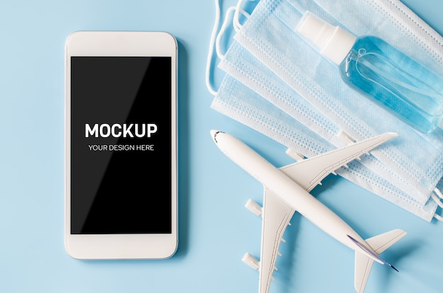 Mock up of smartphone with airplane model, face mask and sanitizer
