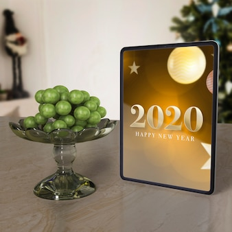 Mock-up tablet with new year wish message on table