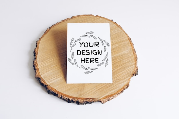 Mock up of vertical postcard on wooden cut tree section on white table. boho design of postcard