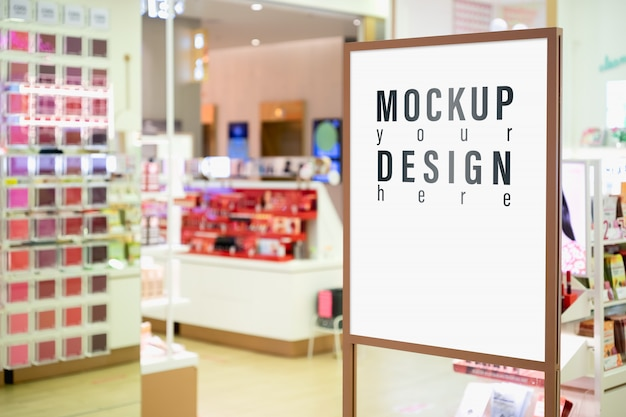 Mock up of vertical sign with blurred cosmetic shop.