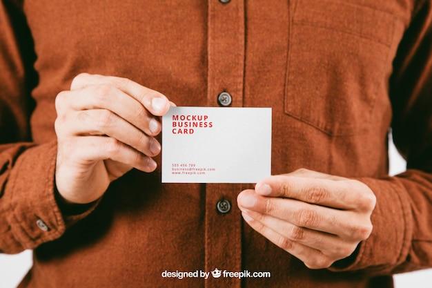 Макет с руки молодого человека с визитной карточкой