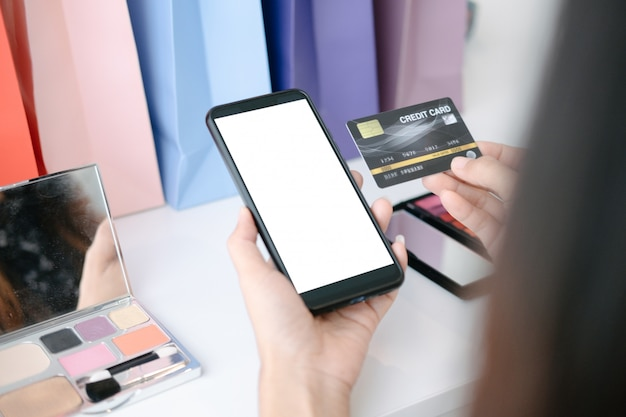 Mockup of beautiful woman holding credit card shopping online with smartphone on online websites