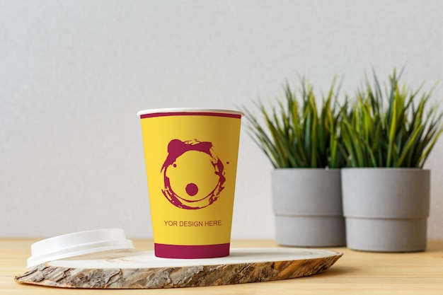 Mockup blank craft paper cup on the white wall background.