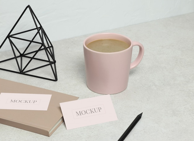 The mockup business card on granite with pink book, black pencil and statuette, cup of coffee