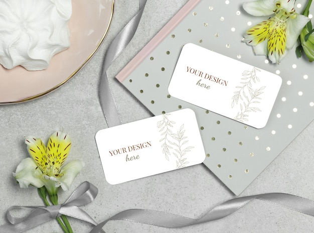 Mockup business card on grey background with flower and ribbon
