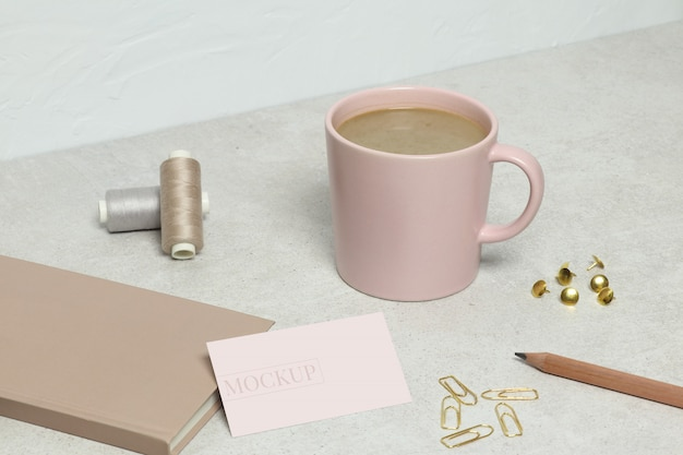 The mockup business card,  pink book, golden pencil, paper clips, pins and threads, cup of coffee  on granite texture