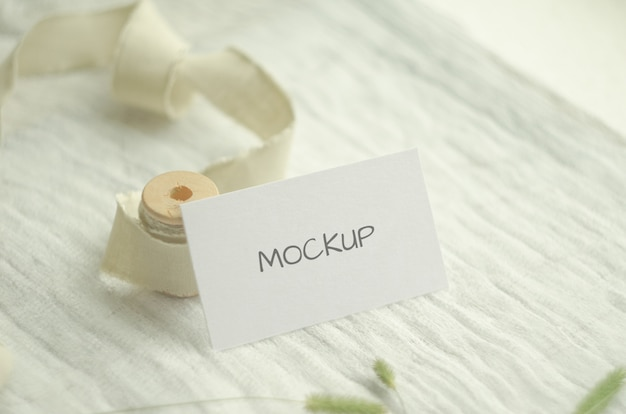 Mockup business card with herbs, vintage spool of cotton braid, on a light space