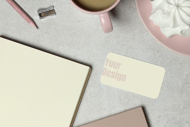 The mockup business card with the note book paper, a pink cup of coffee, the wooden pencil & sharpener