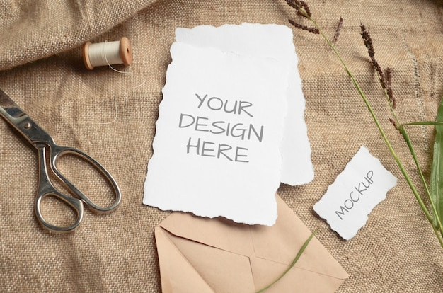 Mockup card greeting card or wedding invitation with jagged edges with herbs, vintage spool on a beige space from burlap fabric