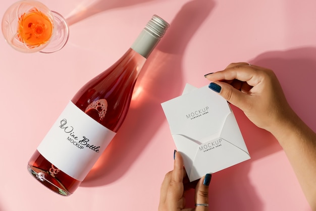 Mockup card in hand with  mockup wine bottle