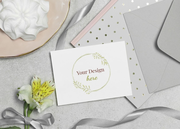 Mockup card with flower, marshmallow and ribbon on grey background