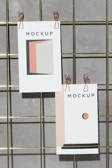 Mockup cards hanging on grid memo board with clips
