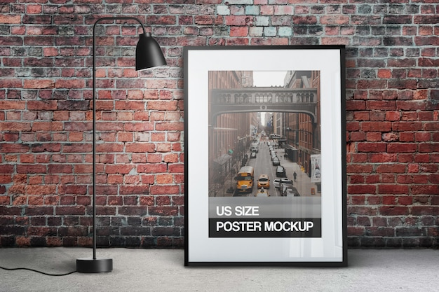 Mockup of clean poster photo in black portrait vertical frame against the brick wall