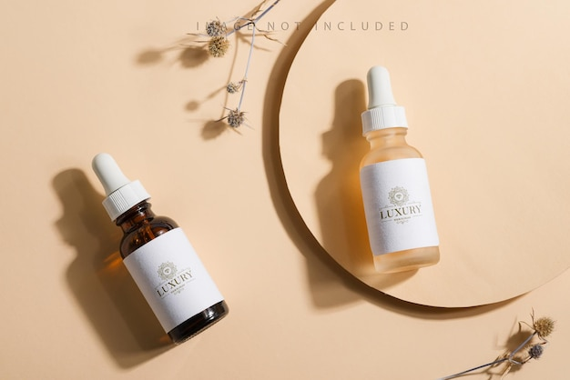 Mockup cosmetic bottles with a dropper on a beige surface with bright sunlight and hard shadows.