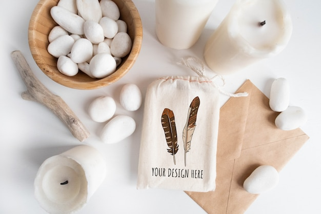 Mockup of cotton bag or pouch and bowl with white pebble and boho elements on white table.