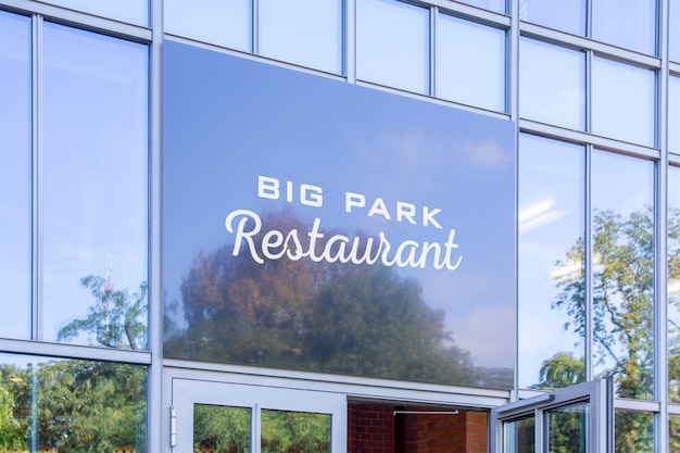 Mockup of dark logo sign on restaurant entrance wall windows