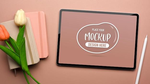 チューリップの花で飾られたピンクのテーブルの上のモックアップデジタルタブレットと日記の本上面図