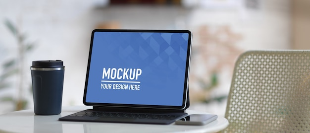 Mockup digital tablet with keyboard and coffee cup on coffee table