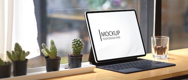 Макет цифрового планшета с клавиатурой на деревянном баре в кафе