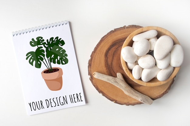 Mockup empty notebook list with a bowl of white pebble and boho rustic decorations on a white table.