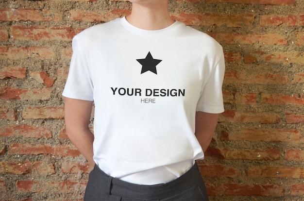 벽돌 벽과 짧은 소매 여성 티셔츠에 로고 이랑