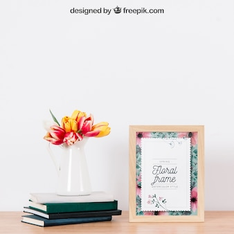 Mockup of frame next to plant on books