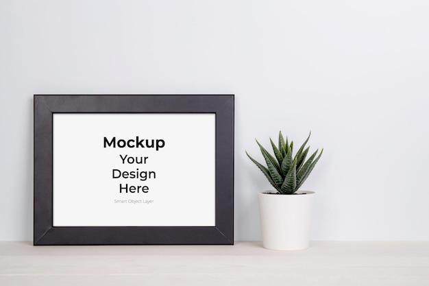 Mockup frame and plants in pot on table