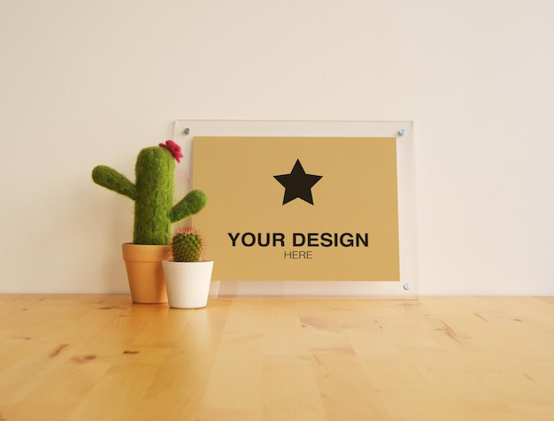 Mockup frame with cactuses on wood table