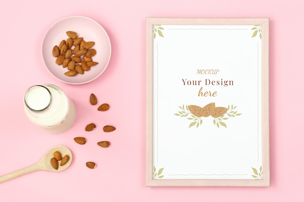 Mockup frame with nuts and bottle of milk on pink background