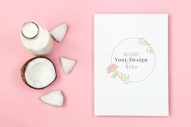 Mockup frame with piece of coconut and bottle of milk on pink background