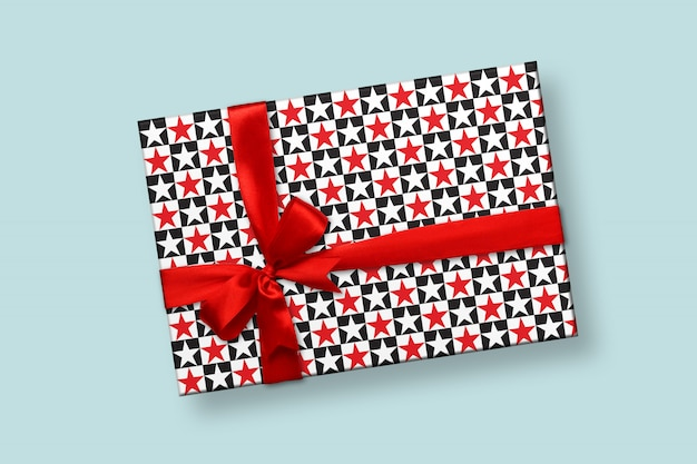 Mockup of gift box with red ribbon and bow, wrapping paper editable