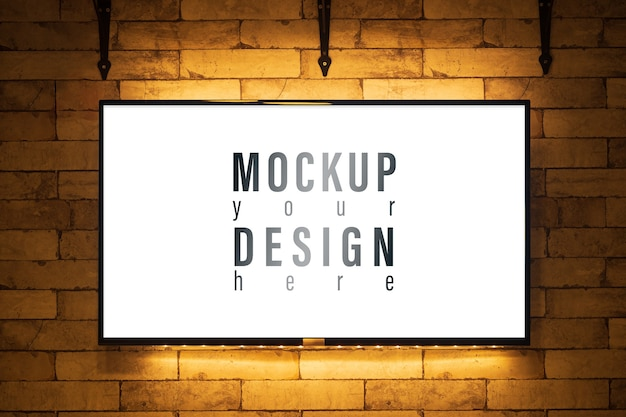 Mockup glowing tv screen on brick wall