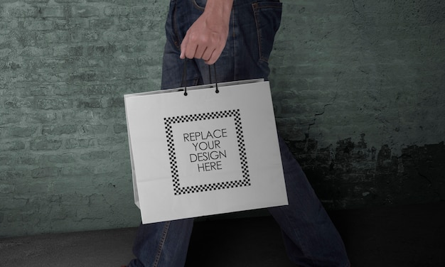 Mockup of hand holding paper tote shopping bag