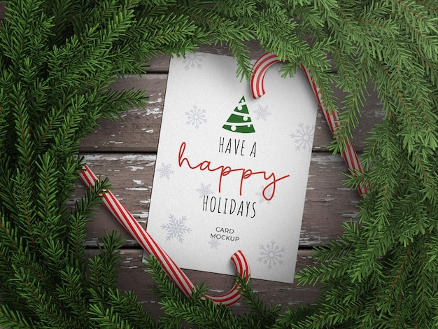 Mockup of holiday greeting card with lollipop cane and christmas wreath decoration on wooden table