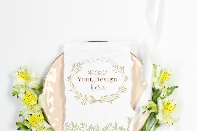 Mockup invitation card with flowers on pink plate