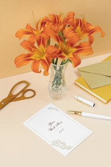Mockup invitation card with orange flowers, notes and gold scissors