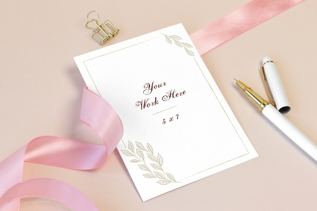 Mockup invitation card with pink ribbon and pen