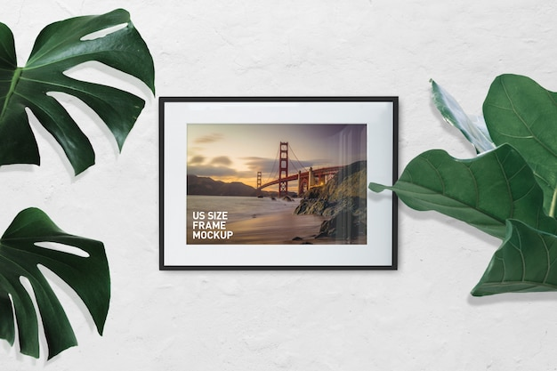 Mockup of landscape photo black frame on white wall with plants