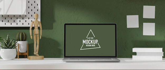 Mockup laptop screen in modern workspace with figure plants and decor on white table and green wall