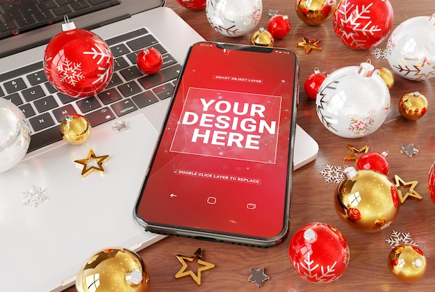 A mockup of mobile phone on desktop with laptop and christmas baubles