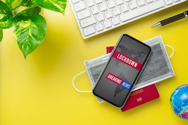 Mockup mobile phone with facial masks and passport on office desk