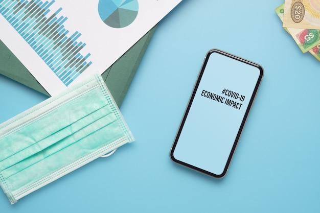 Covid-19経済的影響の概念のためのモックアップ携帯電話。