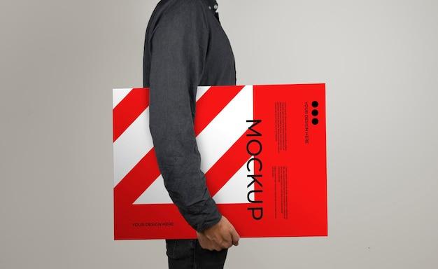 Mockup di un modello che tiene un poster in posizione orizzontale