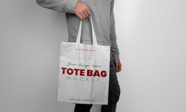 Mockup di modella con in mano una borsa tote bianca