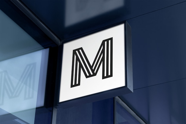 Mockup of modern square hanging logo sign on corporate building facade in black frame