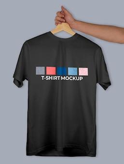 평평한 배경에 손으로 들고 있는 옷걸이에 있는 티셔츠 모형