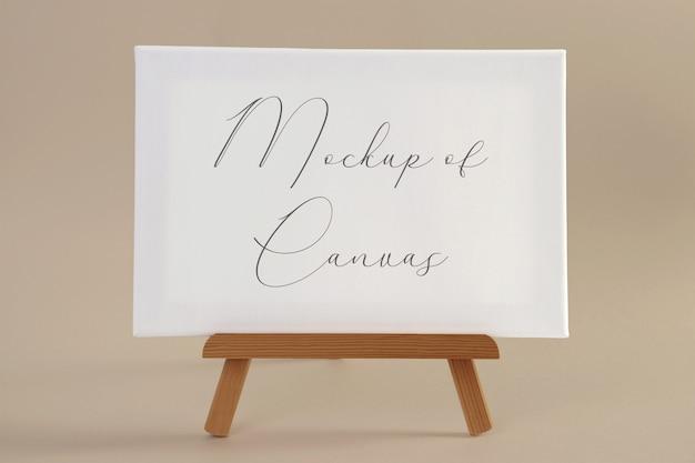 小さな木製イーゼルに白いキャンバスのモックアップ