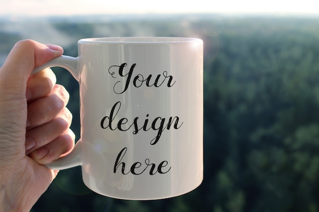 背景の森と手に白いコーヒーのマグカップのモックアップ